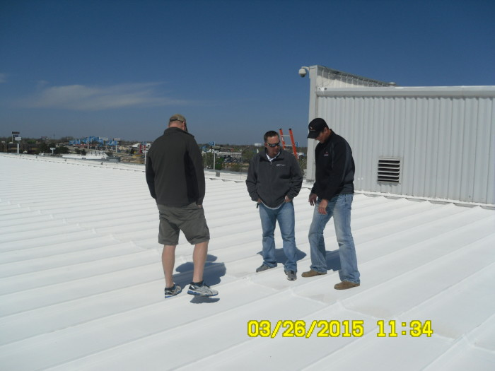 Three workers standing on commercial roof