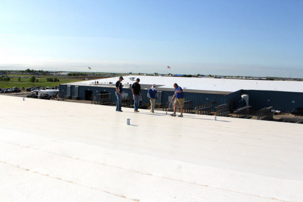 Group of Coryell workers with both newly done roofs in the image