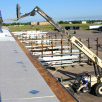 Coryell workers loading roofing materials onto a commercial roof