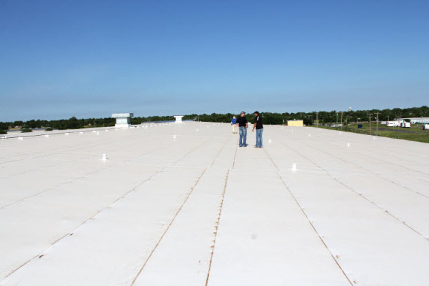 Two Coryell roofers discussing plans on Oklahoma commercial roof