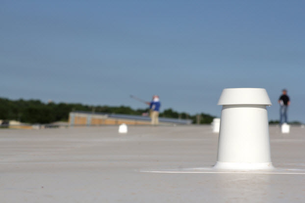 Commercial roofing system with workers in the background