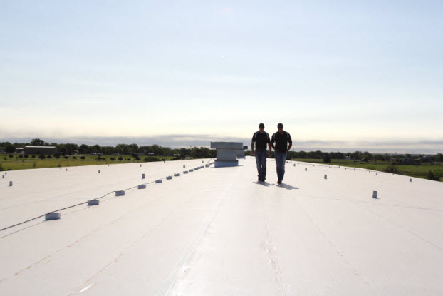 Two roofers inspecting a newly installed roofing system