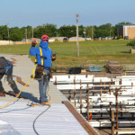 Coryell roofer giving peace sign while installing Duro-Last roofing system
