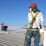 Worker wearing harness while installing commercial Duro-Last Roofing System