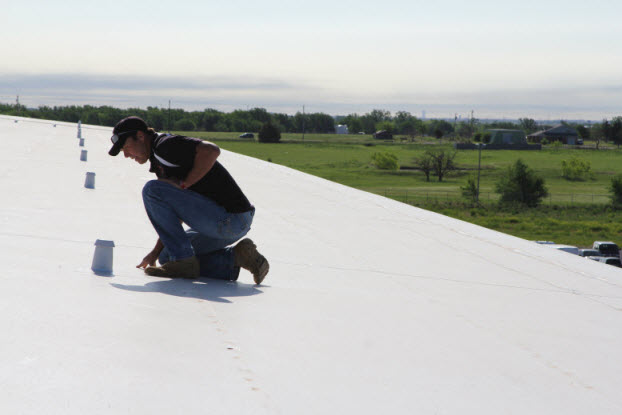 Coreyll Roofing team member inspecting a commercial roof.